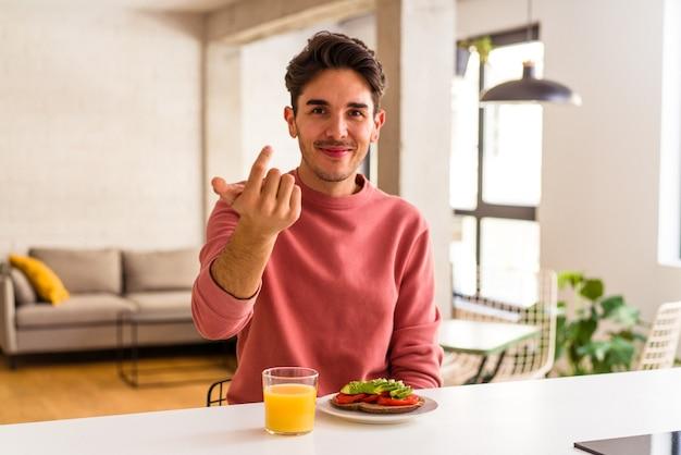 Młody mężczyzna rasy mieszanej jedzący śniadanie w kuchni, wskazując palcem na ciebie, jakby zapraszając podejdź bliżej.