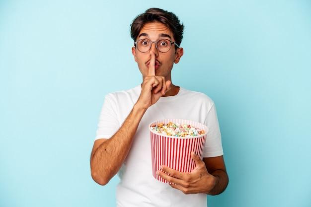 Młody mężczyzna rasy mieszanej jedzenie popcornów na białym tle na niebieskim tle zachowując tajemnicę lub prosząc o ciszę.