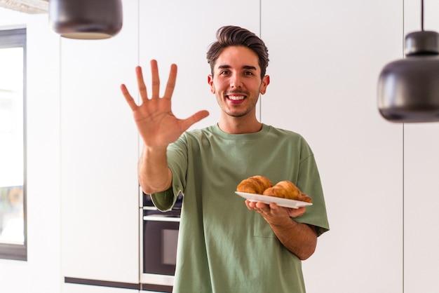 Młody mężczyzna rasy mieszanej jedzenie rogalika w kuchni rano uśmiechając się wesoły pokazując numer pięć palcami.