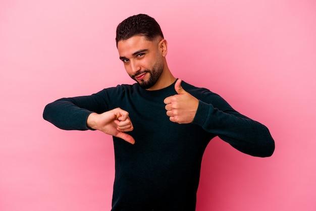 Młody mężczyzna rasy mieszanej na białym tle na różowej ścianie pokazując kciuki w górę i w dół, trudny wybór koncepcji