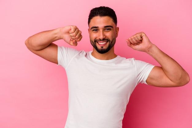 Młody mężczyzna rasy mieszanej na białym tle na różowej ścianie świętuje specjalny dzień, skacze i podnosi ramiona z energią.