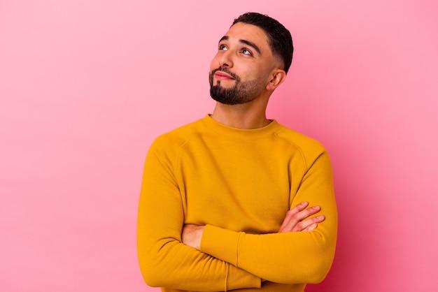 Młody mężczyzna rasy mieszanej na białym tle na różowym tle marzy o osiągnięciu celów i zamierzeń