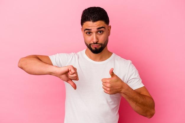 Młody mężczyzna rasy mieszanej na białym tle na różowym tle pokazując kciuki w górę i w dół, trudny wybór koncepcji
