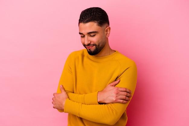 Młody mężczyzna rasy mieszanej na białym tle na różowym tle przytula się, uśmiechając się beztrosko i szczęśliwy.