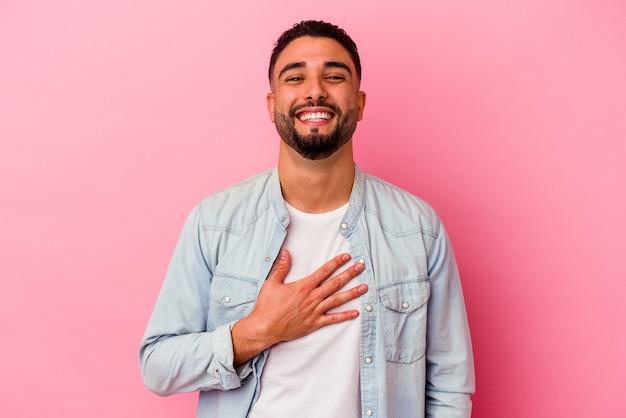 Młody mężczyzna rasy mieszanej na białym tle na różowym tle śmieje się głośno, trzymając rękę na piersi.