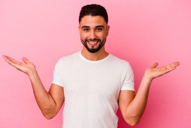 Młody mężczyzna rasy mieszanej na białym tle na różowym tle sprawia, że skala z rękami, czuje się szczęśliwa i pewna siebie.
