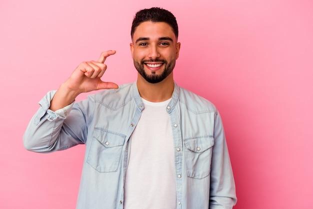 Młody mężczyzna rasy mieszanej na białym tle na różowym tle, trzymając coś małego palcami wskazującymi, uśmiechnięty i pewny siebie.