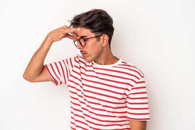 Młody mężczyzna rasy mieszanej na białym tle o ból głowy, dotykając przodu twarzy.