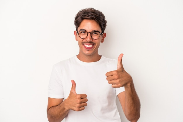 Młody mężczyzna rasy mieszanej na białym tle podnosząc oba kciuki do góry, uśmiechnięty i pewny siebie.