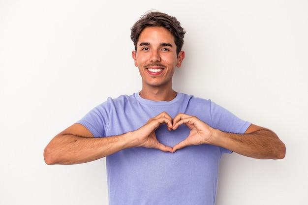 Młody mężczyzna rasy mieszanej na białym tle uśmiechnięty i pokazujący kształt serca rękami.