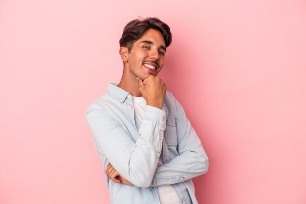 Młody mężczyzna rasy mieszanej na białym tle uśmiechnięty szczęśliwy i pewny siebie, dotykając podbródka ręką.
