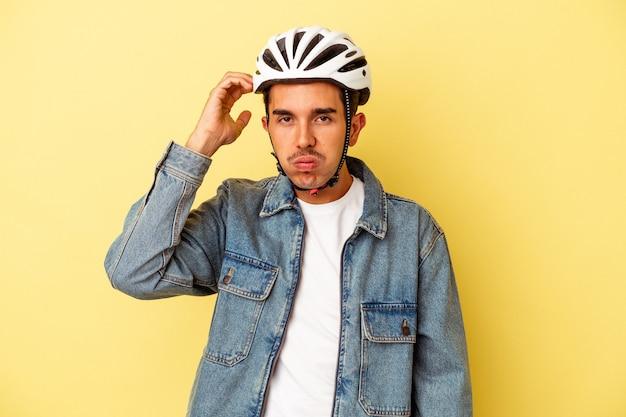 Młody mężczyzna rasy mieszanej noszący kask rowerowy na białym tle na żółtym tle będąc w szoku, pamięta ważne spotkanie.