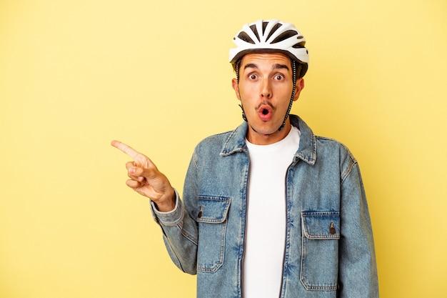 Młody mężczyzna rasy mieszanej noszący kask rowerowy na żółtym tle wskazujący na bok