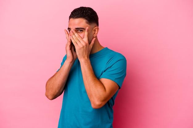 Młody mężczyzna rasy mieszanej, odizolowany na różowym tle, mruga do kamery palcami, zawstydzony zakrywający twarz.
