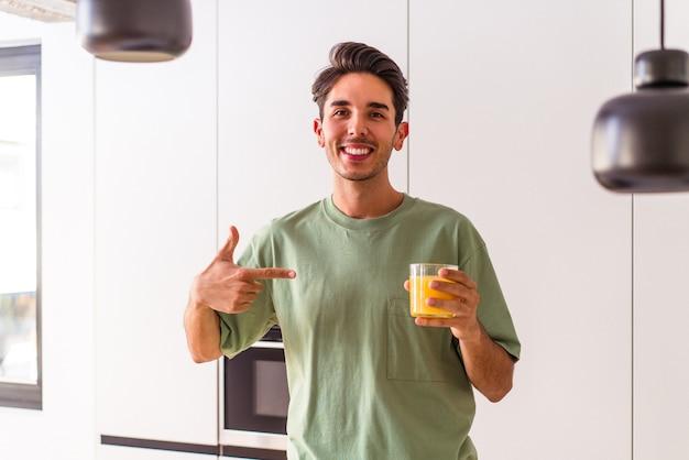 Młody mężczyzna rasy mieszanej pijący sok pomarańczowy w swojej kuchni, wskazujący ręcznie na miejsce na koszulkę, dumny i pewny siebie