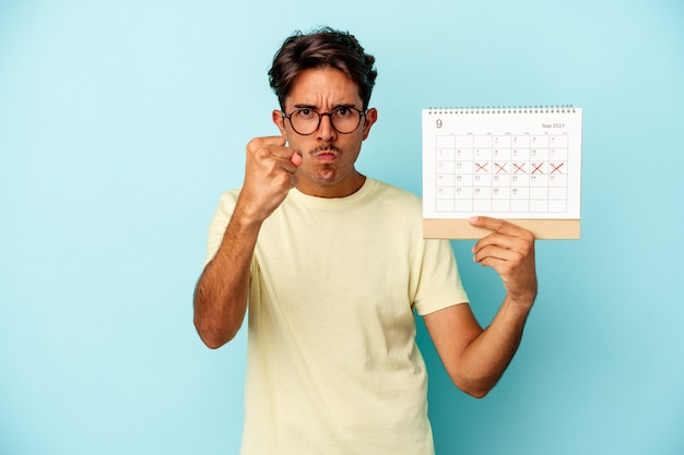 Młody mężczyzna rasy mieszanej posiadający kalendarz na białym tle na niebieskim tle pokazujący pięść do kamery, agresywny wyraz twarzy.