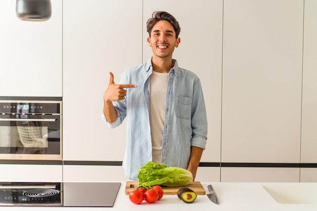 Młody mężczyzna rasy mieszanej, przygotowujący sałatkę na lunch, wskazujący ręcznie na miejsce na koszulkę, dumny i pewny siebie