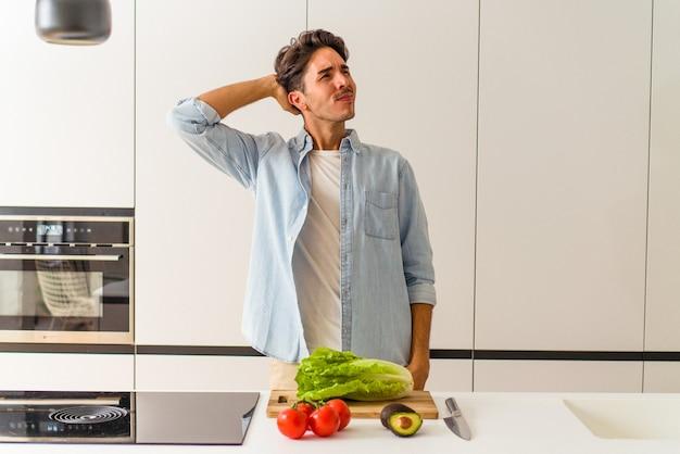 Młody mężczyzna rasy mieszanej przygotowuje sałatkę na lunch dotykając tyłu głowy, myśląc i dokonując wyboru.
