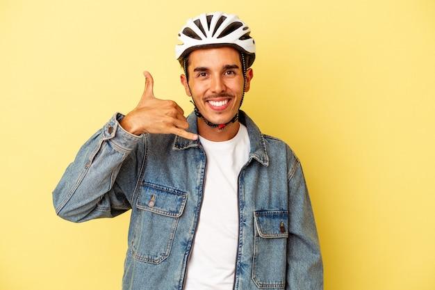Młody mężczyzna rasy mieszanej sobie kask rowerowy na białym tle na żółtym tle pokazując gest połączenia z telefonu komórkowego palcami.