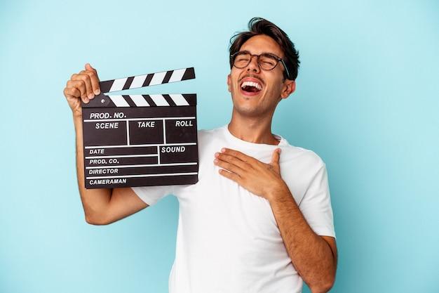 Młody mężczyzna rasy mieszanej trzymając klaps na białym tle na niebieskim tle śmieje się głośno trzymając rękę na klatce piersiowej.