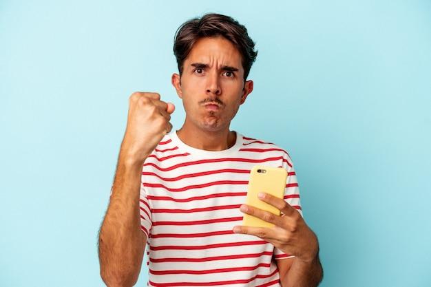Młody mężczyzna rasy mieszanej trzymając telefon komórkowy na białym tle na niebieskim tle pokazując pięść do aparatu, agresywny wyraz twarzy.