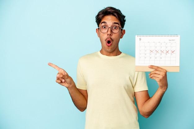 Młody mężczyzna rasy mieszanej trzymający kalendarz na białym tle na niebieskim tle wskazujący na bok