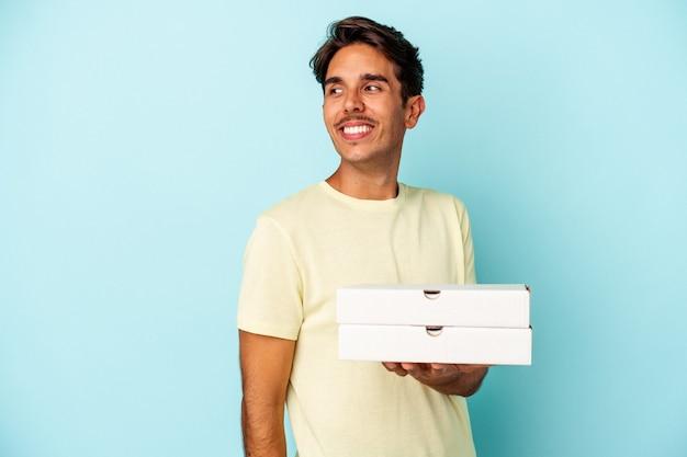 Młody mężczyzna rasy mieszanej trzymający pizze na białym tle na niebieskim tle wygląda na uśmiechnięty, wesoły i przyjemny.