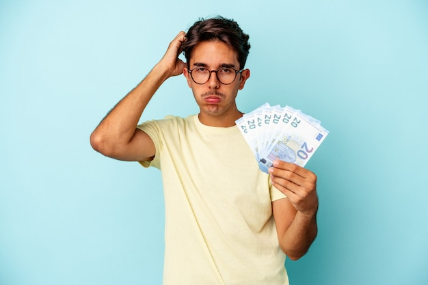 Młody mężczyzna rasy mieszanej, trzymający rachunki na białym tle na niebieskim tle, będąc w szoku, przypomniała sobie ważne spotkanie.