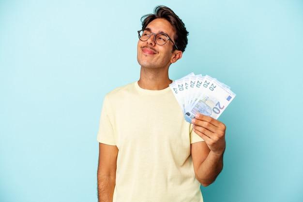 Młody mężczyzna rasy mieszanej, trzymający rachunki na białym tle na niebieskim tle, marzący o osiągnięciu celów i celów
