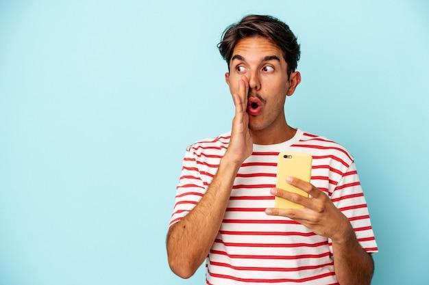 Młody mężczyzna rasy mieszanej trzymający telefon komórkowy na białym tle na niebieskim tle mówi tajne gorące wiadomości o hamowaniu i patrzy na bok
