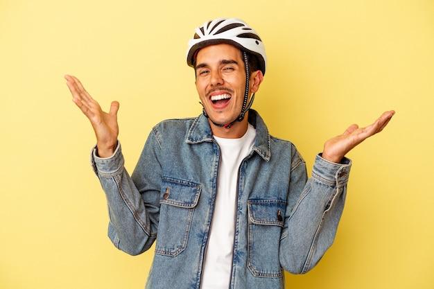 Młody mężczyzna rasy mieszanej ubrany w kask rowerowy na białym tle na żółtym tle otrzymujący miłą niespodziankę, podekscytowany i podnoszący ręce.