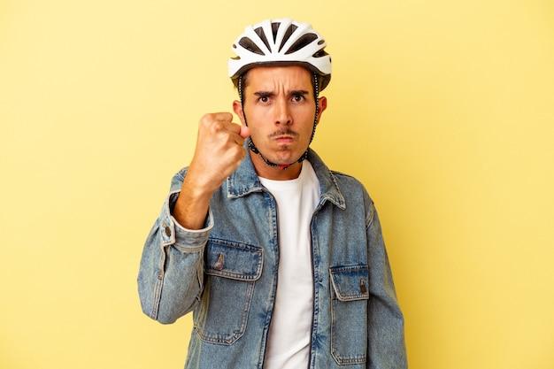 Młody mężczyzna rasy mieszanej w kasku rowerowym na białym tle na żółtym tle pokazujący pięść do aparatu, agresywny wyraz twarzy.