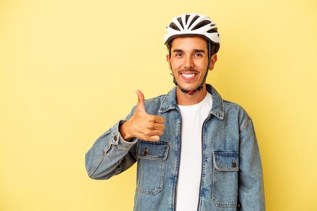 Młody mężczyzna rasy mieszanej w kasku rowerowym na żółtym tle uśmiechający się i podnoszący kciuk w górę