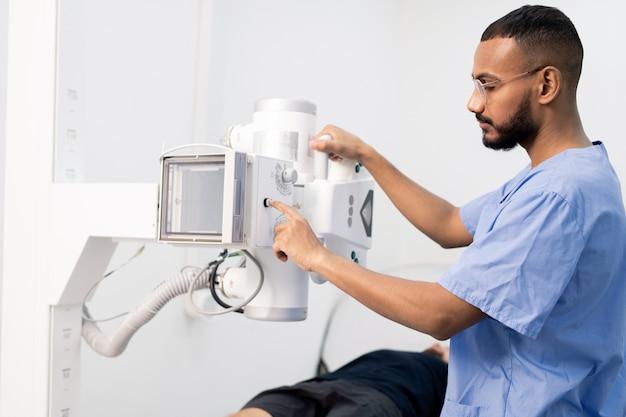 Młody mężczyzna rasy mieszanej w niebieskim mundurze, naciskając przycisk na nowy sprzęt medyczny podczas pracy w klinikach