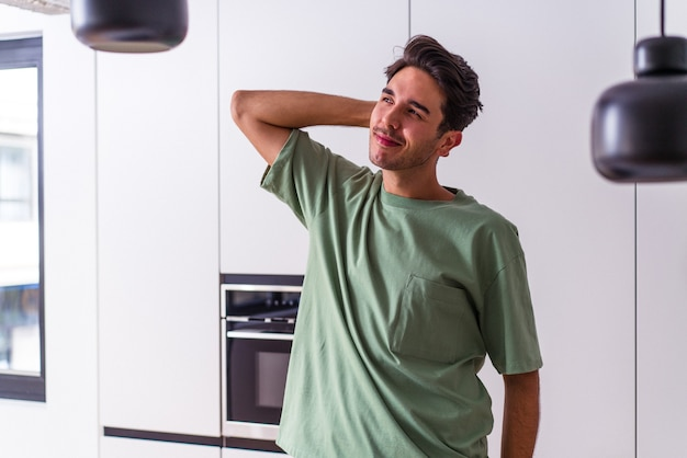 Młody mężczyzna rasy mieszanej w swojej kuchni dotyka tyłem głowy, myśli i dokonuje wyboru.
