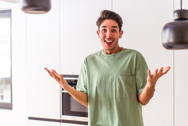 Młody mężczyzna rasy mieszanej w swojej kuchni otrzymuje miłą niespodziankę, podekscytowany i podnoszący ręce.