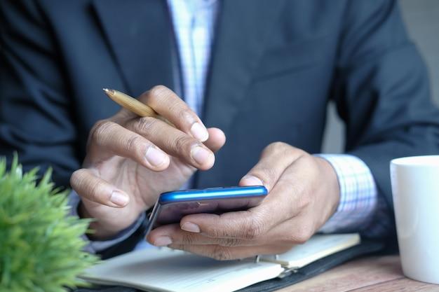 Młody mężczyzna ręka za pomocą smartfona i pisanie na notatniku przy biurku