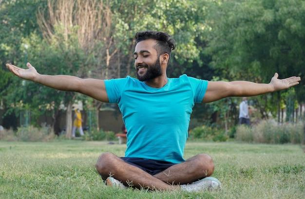 Młody mężczyzna relaksujący się i stresujący z mniej skrzyżowanym siadaniem w parku