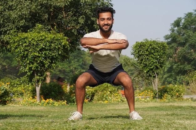 Młody mężczyzna robi ćwiczenia treningowe rano w parku