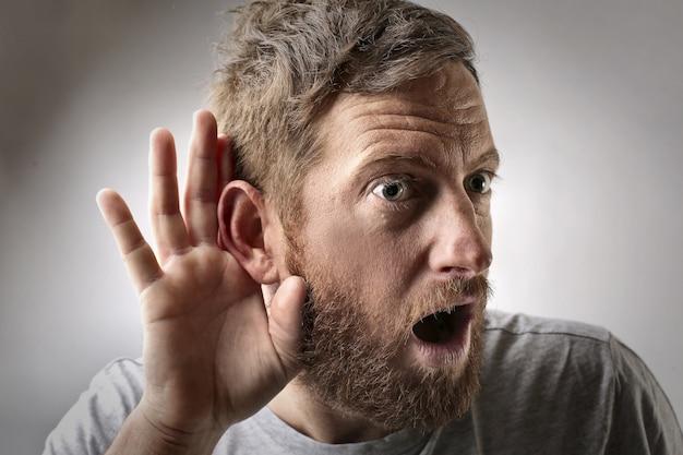 Młody mężczyzna robi gest słuchania