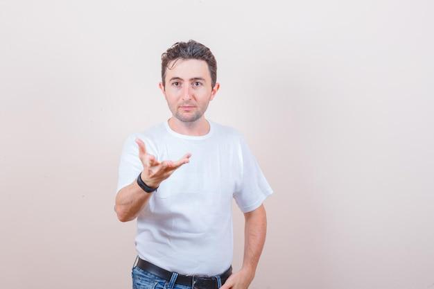 Młody mężczyzna robi gest zadawania pytań w białej koszulce, dżinsach i wygląda na zdziwionego