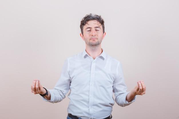Młody mężczyzna robi medytację z zamkniętymi oczami w białej koszuli i wygląda spokojnie