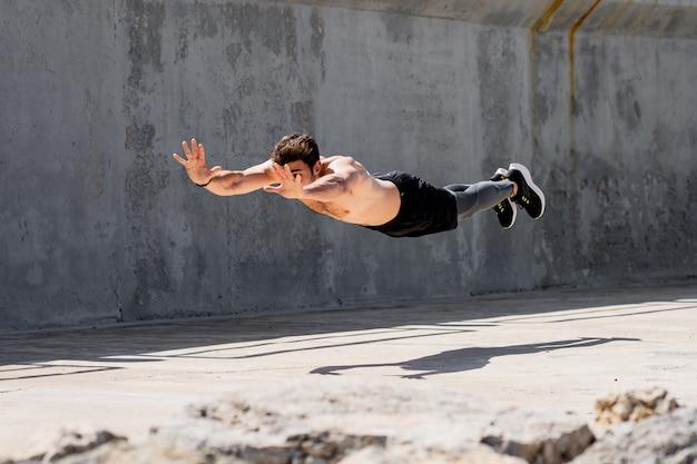 Młody mężczyzna robi pompki ze skokiem bez koszuli na ulicy