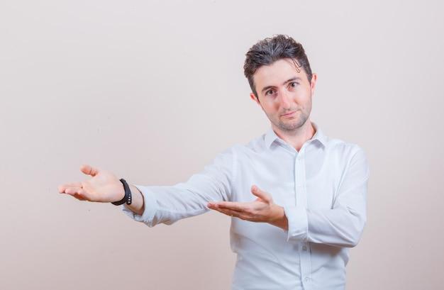 Młody mężczyzna robi powitalny gest w białej koszuli i wygląda delikatnie