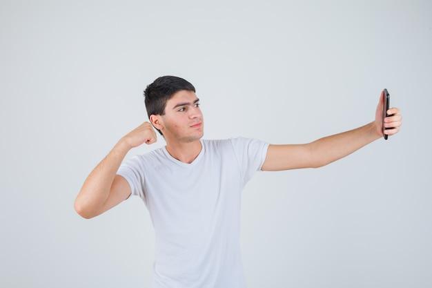 Młody mężczyzna robi selfie, pokazując mięśnie ramion w koszulce i patrząc wesoło. przedni widok.