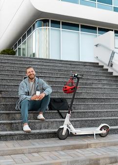 Młody mężczyzna robi sobie przerwę po jeździe na skuterze