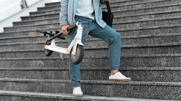 Młody mężczyzna robi sobie przerwę po jeździe skuterem na świeżym powietrzu