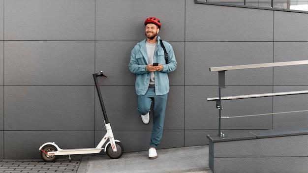 Młody mężczyzna robi sobie przerwę po jeździe skuterem na zewnątrz