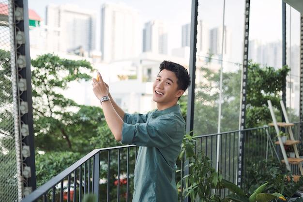 Młody mężczyzna robi telefonem zdjęcia pięknego widoku z hotelowego balkonu