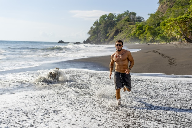 Młody mężczyzna robi trening biegowy na plaży